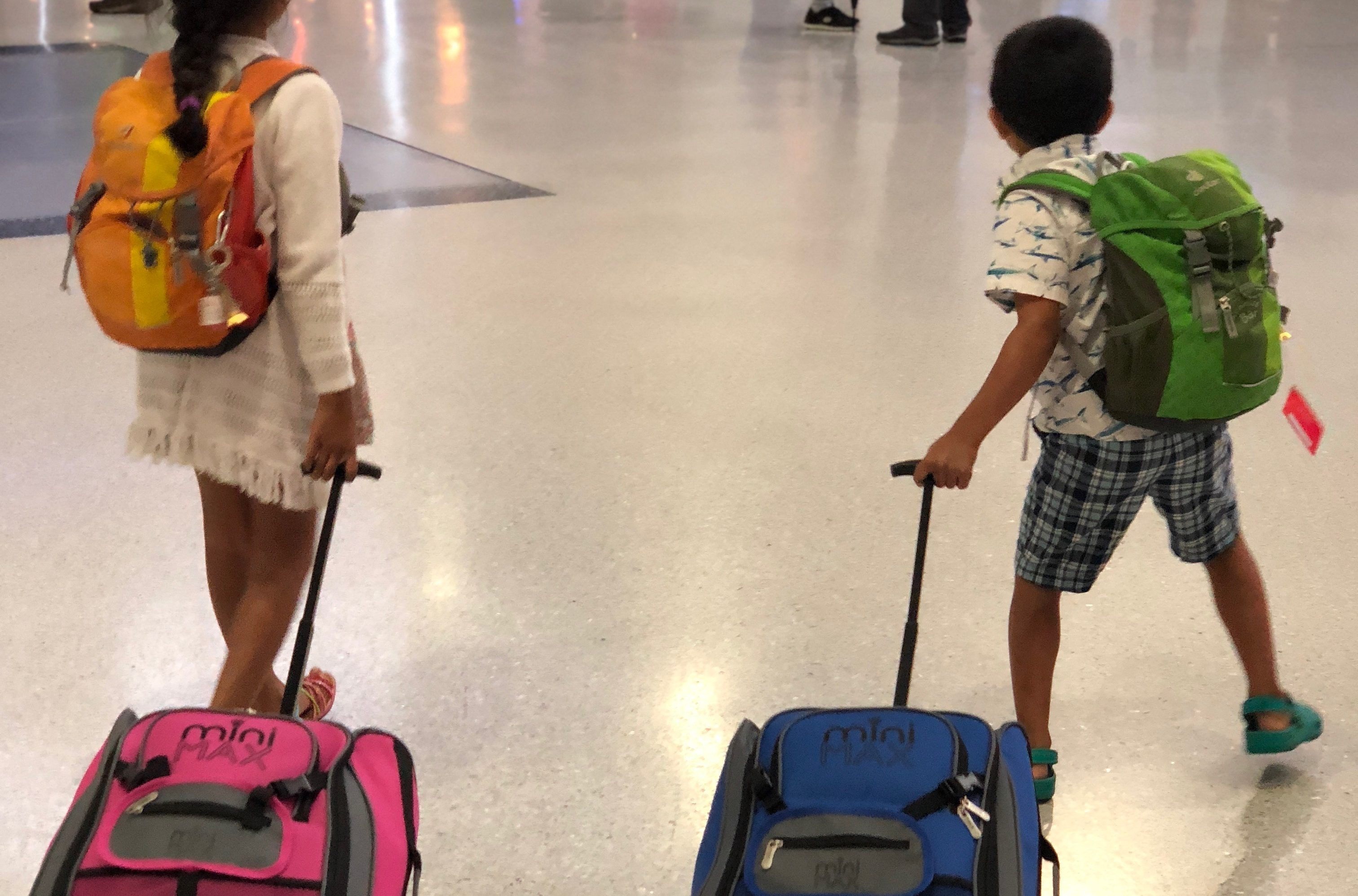 kids at an airport, with backpacks and suitcases